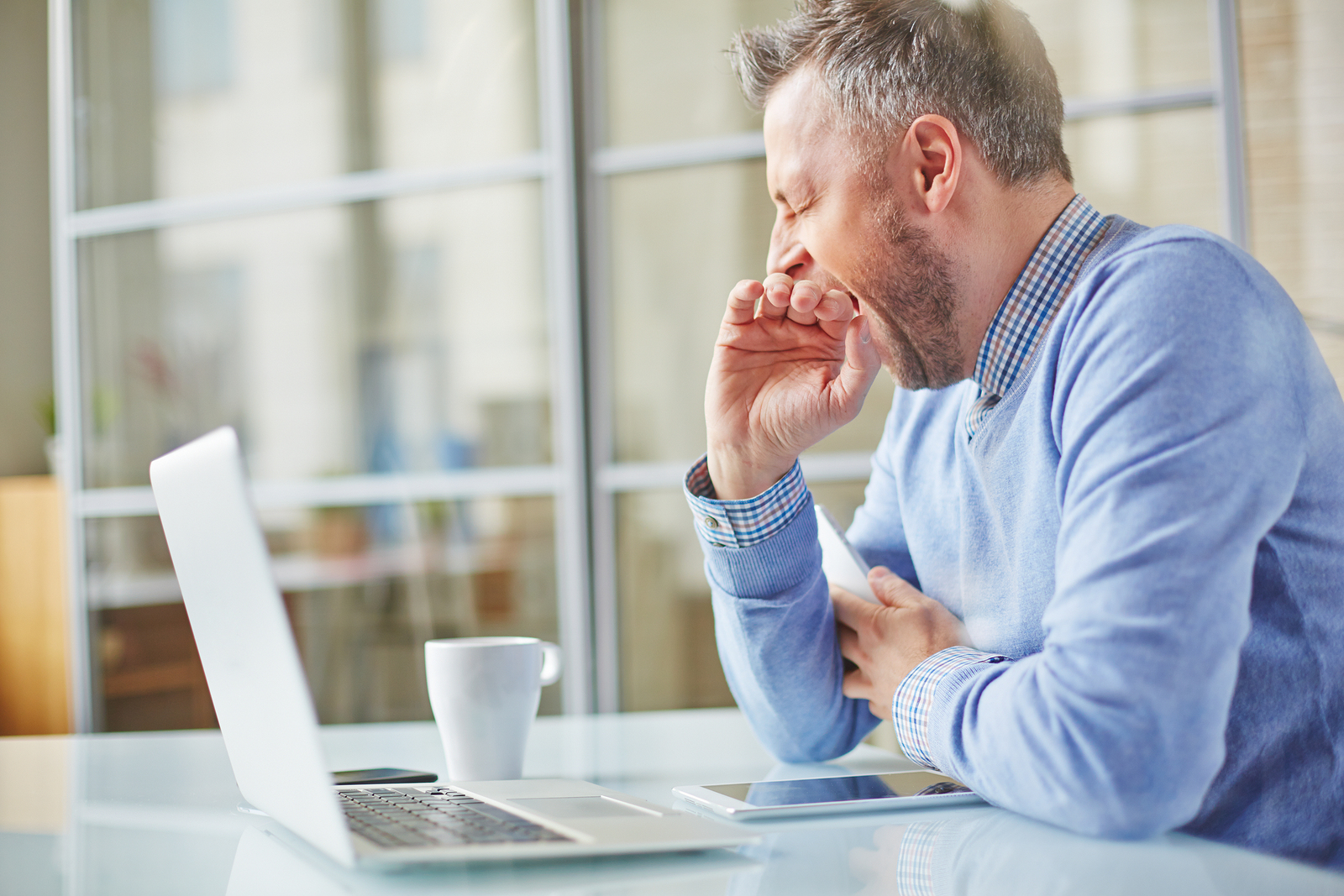 Tired man yawning at workplace in office